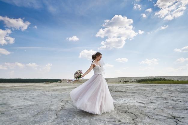 Sposa della donna in vestito da sposa nella danza del deserto