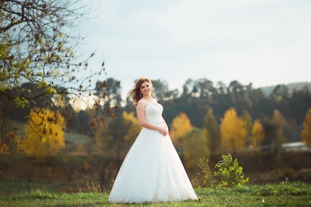 Sposa di bellezza in abito da sposa con velo bouquet e pizzo sulla natura. ragazza bellissima modella in un abito da sposa bianco. ritratto femminile nel parco. donna con acconciatura. signora carina all'aperto