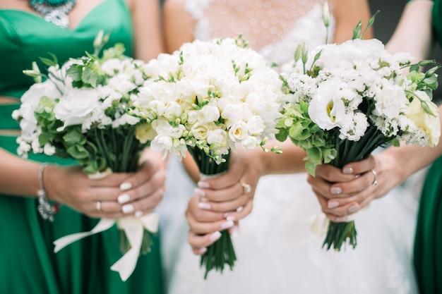 Sposa e damigelle che tengono bellissimi fiori