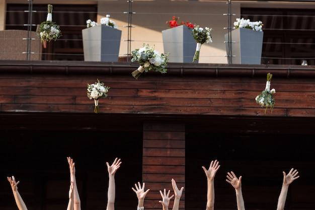 Sposa e damigelle che tirano su i mazzi di fiori, momento gioioso.