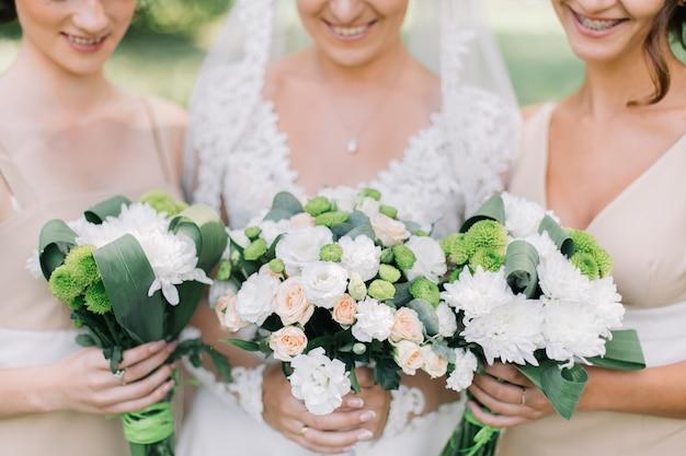 Sposa e damigelle d'onore che tengono il primo piano dei mazzi