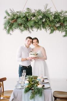 Sposa e sposo affascinanti che sorridono al tavolo nella sala per banchetti e che tengono torta nuziale decorata con bacche e cotone