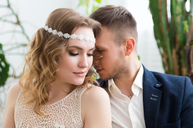Sposa e sposo affascinanti sulla loro celebrazione di nozze in un interno lussuoso.