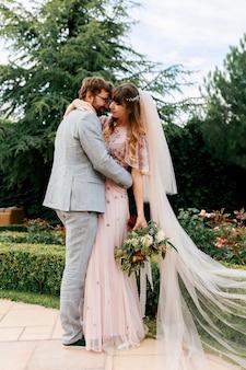 Sposa e sposo al giorno delle nozze camminando all'aperto sulla natura primaverile. newlywed felice donna e uomo che abbracciano nel parco verde. coppia di innamorati matrimonio.