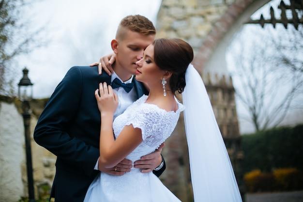 Sposa e sposo al giorno delle nozze che camminano all'aperto. matrimonio. coppia di innamorati, sposi felici donna e uomo che abbraccia nel parco verde. sposi all'aperto. serie. focalizzazione morbida