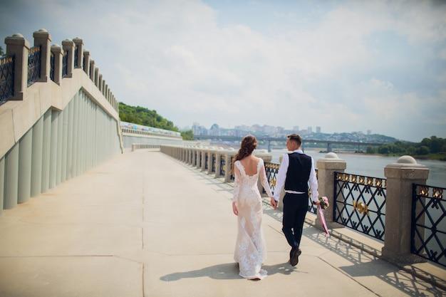 Sposa e sposo alla moda che posano sullo sfondo del fiume.