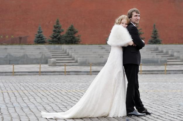 Sposa e sposo che abbracciano all'aperto