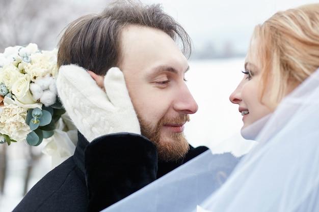 Sposa e sposo che abbracciano e baciano mentre in piedi sulla strada in inverno