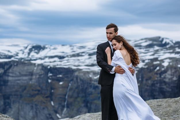 Sposa e sposo che abbracciano in alto nelle montagne