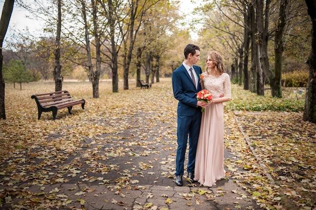 Sposa e sposo che abbracciano in una foresta nella foresta di autunno, passeggiata di nozze.
