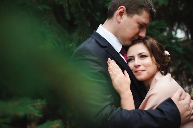 Sposa e sposo che abbracciano in una foresta nella foresta di autunno, passeggiata di nozze