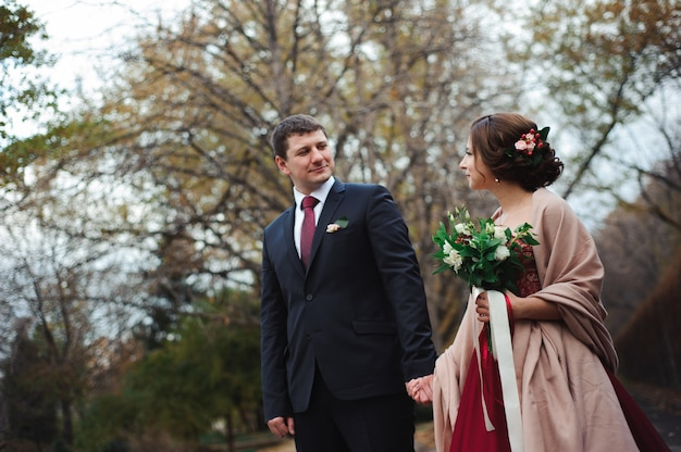Sposa e sposo che abbracciano in una foresta nella foresta di autunno
