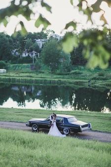 Sposa e sposo che abbracciano vicino alla vecchia retro automobile