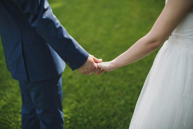Sposa e sposo che camminano insieme tenendo le mani