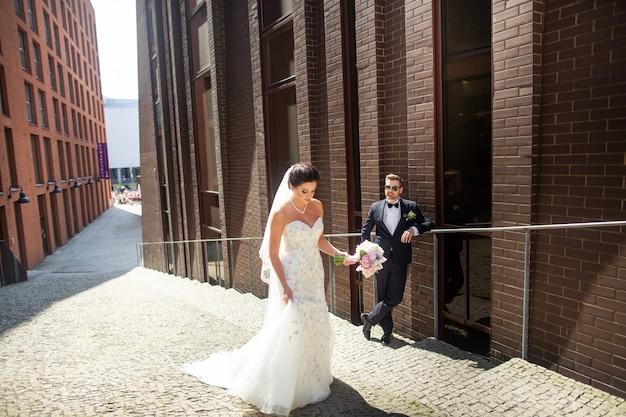 Sposa e sposo che camminano nella città, giorno delle nozze, matrimonio. sposi a urban. giovane coppia nel giorno del matrimonio.