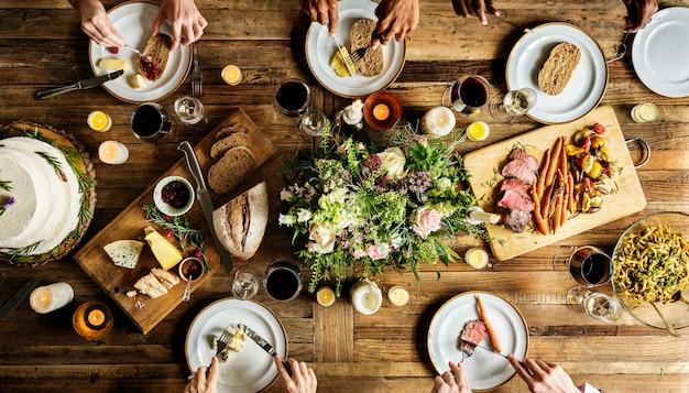 Sposa e sposo che hanno il pasto con gli amici al ricevimento di nozze