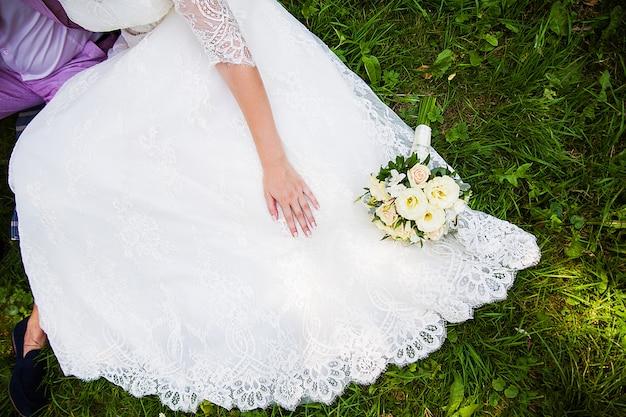 Sposa e sposo che si siedono sull'erba con il bello mazzo