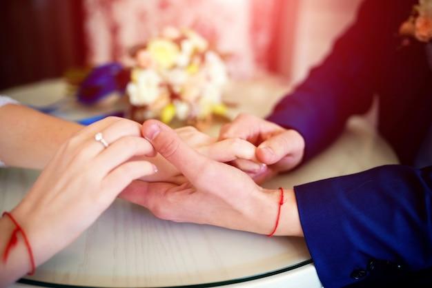 Sposa e sposo che si tengono per mano con le fedi nuziali sulla tavola sopra sfuocatura
