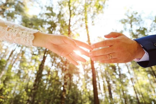 Sposa e sposo che si tengono per mano nel parco.