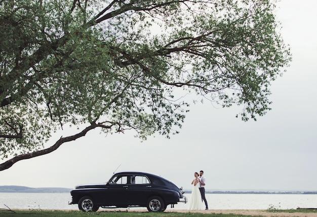 Sposa e sposo che stanno vicino ad una retro automobile