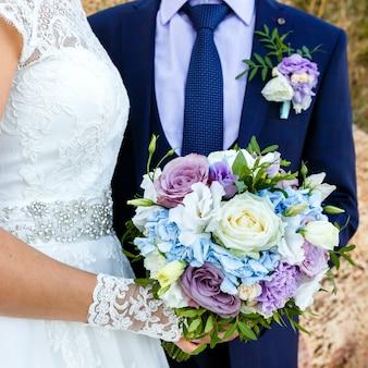 Sposa e sposo che tengono bello mazzo di rose all'aperto. cornice quadrata