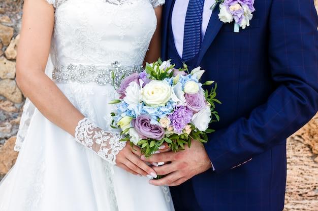 Sposa e sposo che tengono bello mazzo di rose all'aperto.
