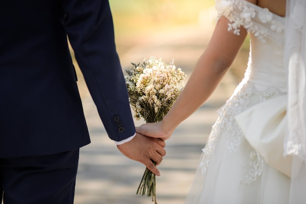Sposa e sposo che tengono le mani all'aperto nell'evento di nozze