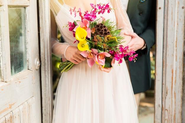 Sposa e sposo con bouquet da sposa di fiori