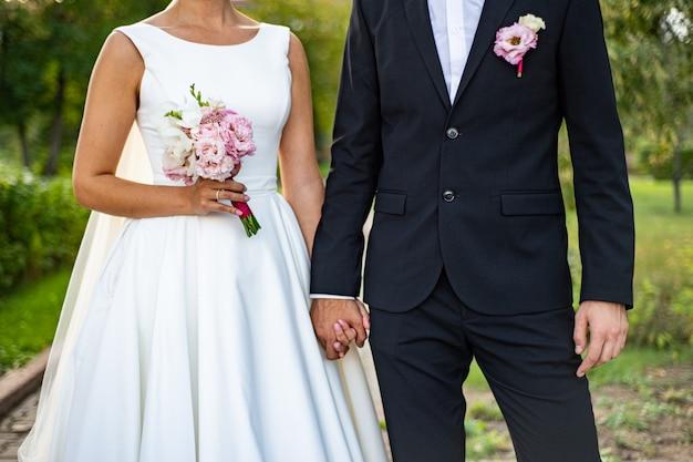 Sposa e sposo con un bouquet. la sposa in un abito bianco peloso, lo sposo in un completo da smoking blu.