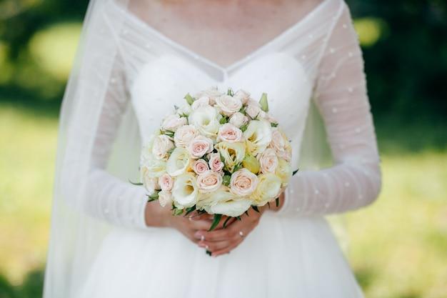 Sposa e sposo con un mazzo di fiori rossi e verdi in mano