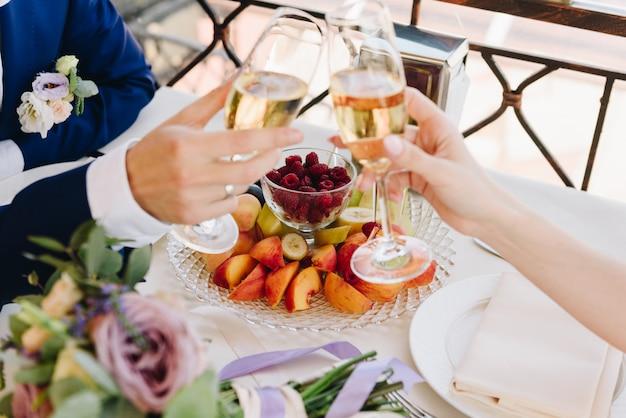 Sposa e sposo della persona appena sposata che mangiano frutta e che bevono champagne il giorno delle nozze