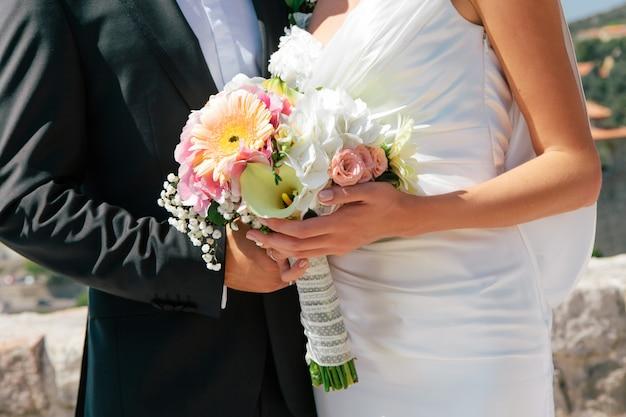 Sposa e sposo della persona appena sposata del primo piano che abbracciano e che tengono il mazzo di nozze in mani, fuoco selettivo