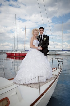 Sposa e sposo felici che abbracciano su uno yacht