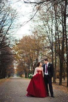 Sposa e sposo felici che camminano nella foresta di autunno