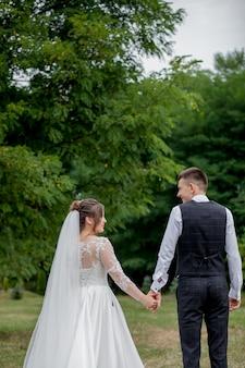 Sposa e sposo felici che si tengono per mano e che camminano nel giorno delle nozze del giardino. punto di vista posteriore degli sposi alla moda affascinanti che si tengono per mano mentre camminando nella foresta del parco, momenti felici di matrimonio