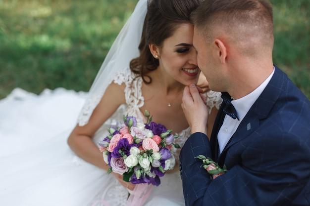 Sposa e sposo felici dopo cerimonia di nozze in natura. sposi sorridenti che si abbracciano e sorridono a vicenda all'aperto da vicino. giorno del matrimonio.