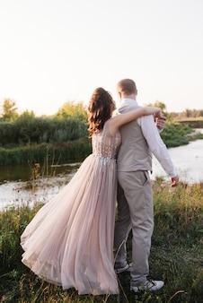 Sposa e sposo in posa attraverso il campo vicino al fiume