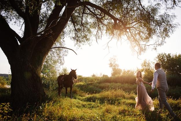 Sposa e sposo in posa attraverso il campo