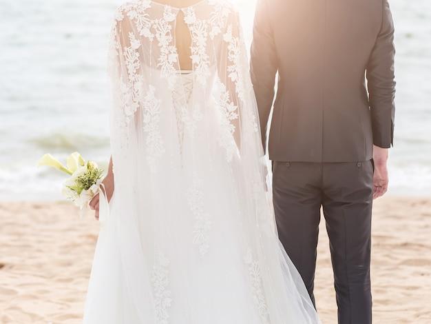 Sposa e sposo sulla spiaggia con un momento romantico