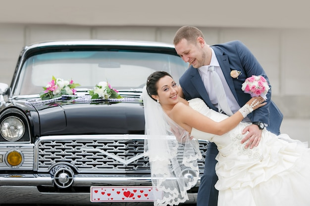 Sposa e sposo sulla strada vicino alla macchina retrò