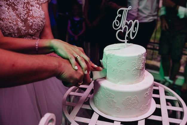 Sposa e sposo taglio elegante semplice torta nuziale con un cappello decorato