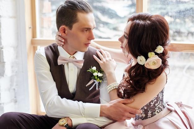 Sposa e sposo vicino alla grande finestra che abbraccia amore