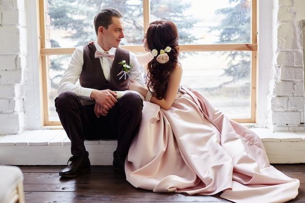 Sposa e sposo vicino alla grande finestra che abbraccia prima del matrimonio. amore e tenerezza in ogni aspetto