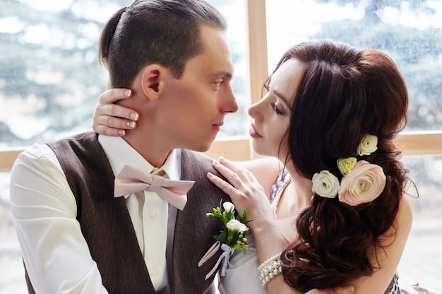 Sposa e sposo vicino alla grande finestra che abbracciano le nozze