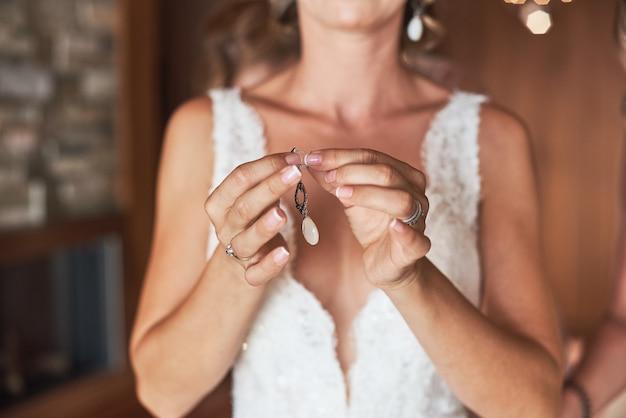 Sposa elegante mettendo su orecchini, preparando per il matrimonio.