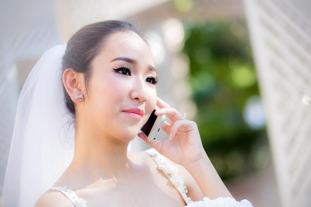 Sposa felice che parla sul telefono cellulare in vestito da sposa