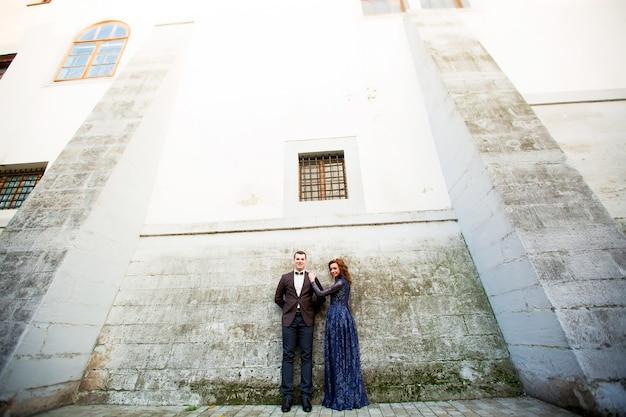 Sposa felice che sta al sorridere grigio della parete
