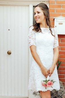 Sposa felice che tiene il suo piccolo mazzo di nozze delle rose rosa in porta bianca. concetto di giorno del matrimonio.