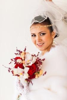 Sposa felice con lo sposo aspettante dei gioielli del diamante e del mazzo nel giorno delle nozze di inverno