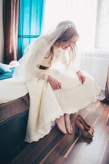 Sposa felice della ragazza di bello sorriso felice. guarda le scarpe marroni. preparare la scarpa.